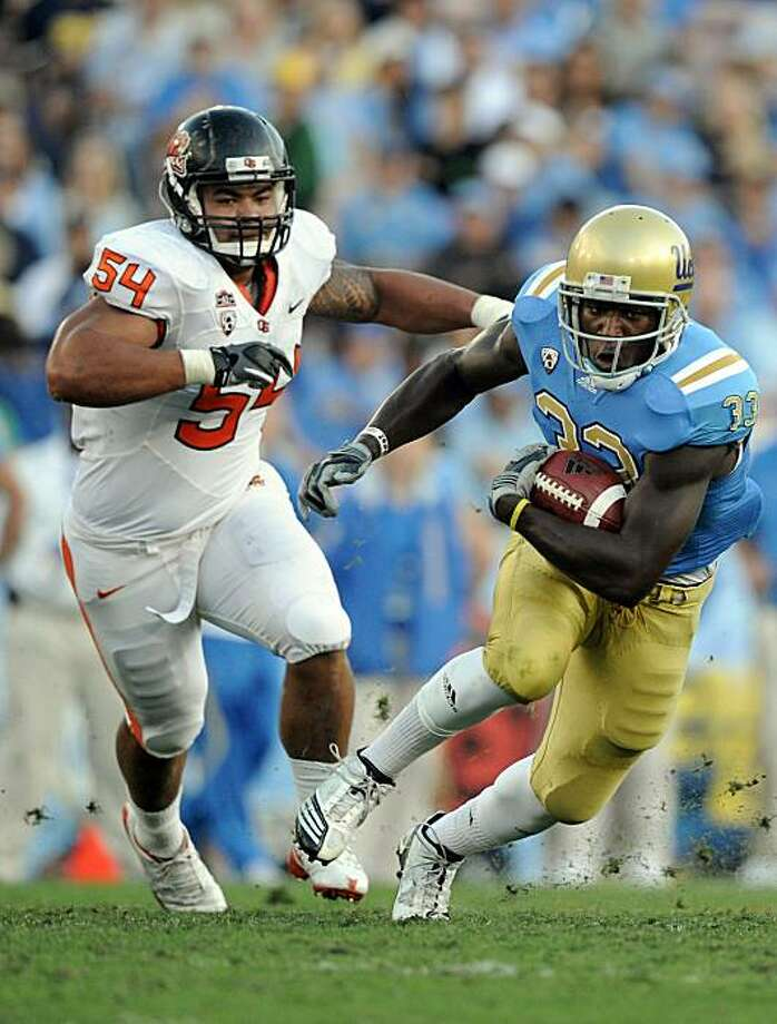 PASADENA, CA - NOVEMBER 06:  Derrick Coleman #33 of the UCLA Bruins runs away from Stephen Paea #54 of the Oregon State Beavers during the second quarter at the Rose Bowl on November 6, 2010 in Pasadena, California. Photo: Harry How, Getty Images