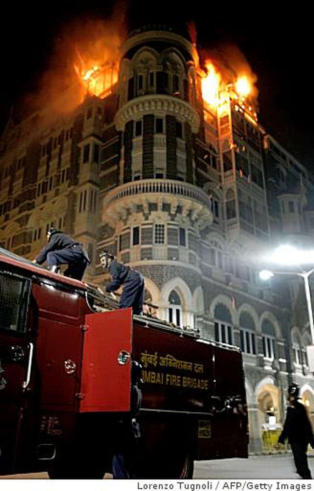 Fire brigade personel arrive as fire engulfs the top floor of the Taj Mahal hotel, site of one of the shootouts with terrorists during a in Mumbai on late November 26, 2008. Nearly 80 people were killed and an estimated 200 to 350 injured in a series of coordinated attacks in the Indian city of Mumbai late November 26, as heavily armed Islamist militants hit two luxury hotels and took foreign guests hostage. AFP PHOTO/ Lorenzo TUGNOLI (Photo credit should read LORENZO TUGNOLI/AFP/Getty Images)