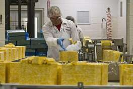 Dennis Schaefer tosses some slices of cheese at the Sargento Cheese Company Friday, Nov. 12, 2010, in Plymouth, Wis. While the sluggish economy has taken a toll on manufacturing and related industries, one sector has remained a bright spot over the last few years: food production.