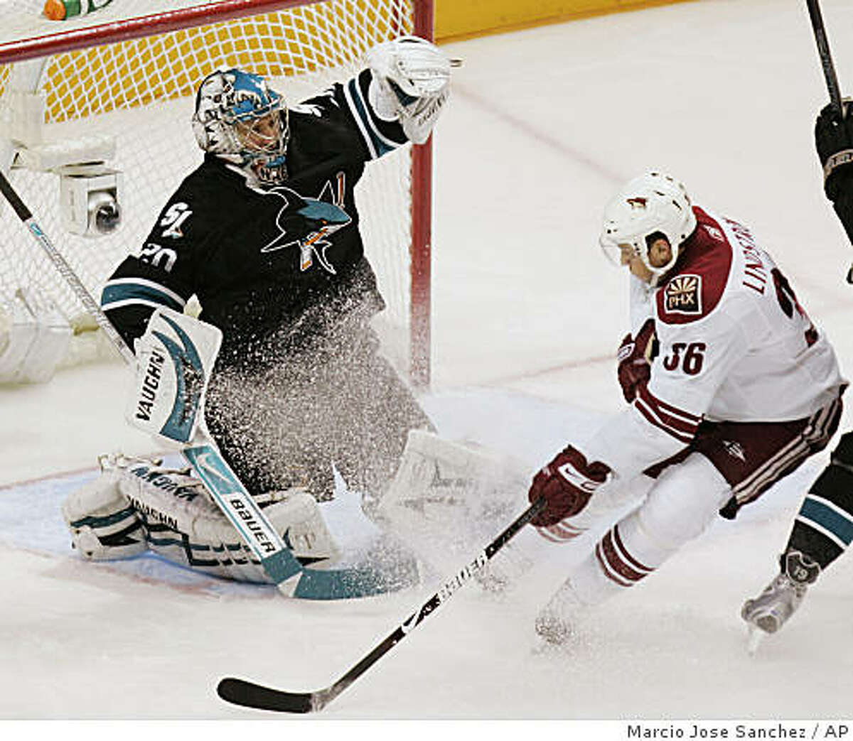 San Jose Sharks goalie Evgeni Nabokov, left, stops a shot from Phoenix Coyotes left wing Joakim Lindstrom during the first period.