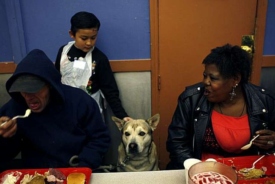 Dylan Henry (center), one of the volunteers, pets a service dog while Edward Placek (left) and Sheryl Woolery (right) enjoy a Thanksgiving meal at Glide Memorial Church in San Francisco on Thursday. Photo: Michelle Gachet, The Chronicle