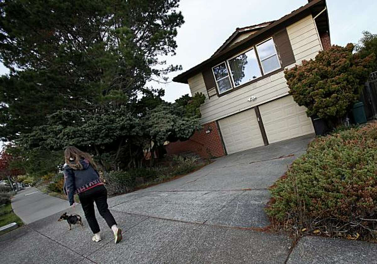 Sarah Gerke walks the family dog Hugo past her home Tuesday November 23, 2010. Susan and Robert Gerke thought they were doing everything their bank, CitiMortgage, wanted them to do to get a loan modification on their San Rafael, Calif. home. Now the bank is set to foreclose on the family which includes their daughter Sarah, and father Robert.