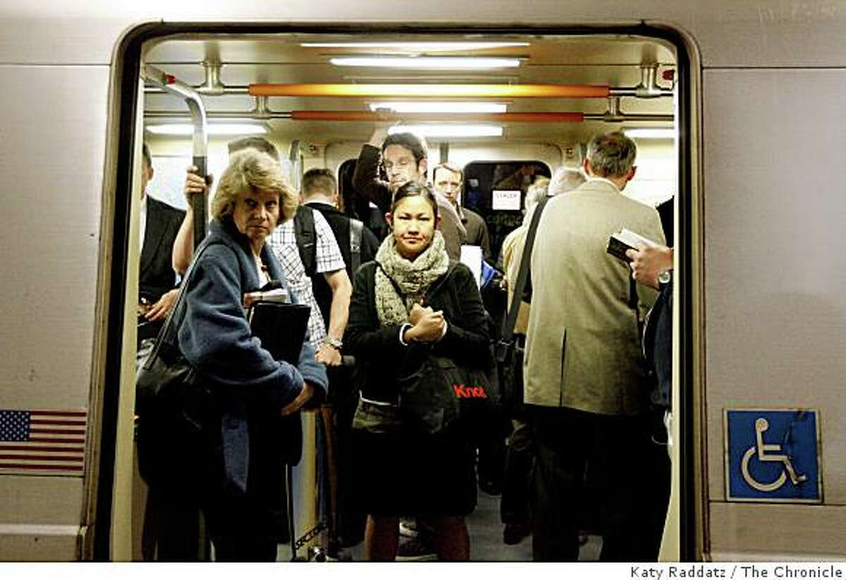 Commuters at Embarcadero Station crowd into a BART car in San Francisco, Calif. BART trains are being reconfigured to pack in more commuters by removing some seats and adding hanging hold straps.Katy Raddatz / The San Francisco Chronicle