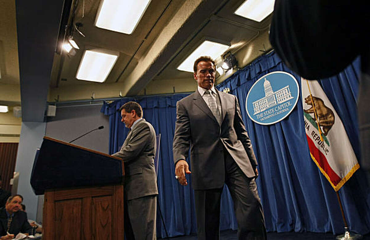 Finance Director Mike Genest walks up to the podium after Governor Arnold Schwarzenegger walks off stage during his presentation of the latest revised versions of the California State Budget Thursday May 14, 2009 during a press conference at the State Capital in Sacramento.