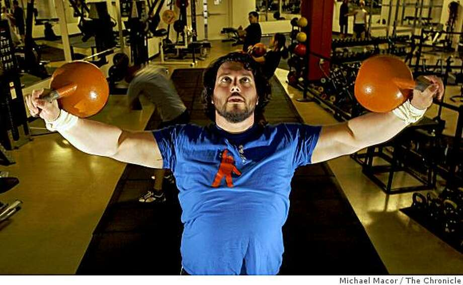 """John Wild Buckley, displays the """"Iron Cross"""" using kettlebells,on Wednesday April 1, 2009.  Buckley teaches workshops on training using weights at the Breakaway Performance Center in San Francisco, Calif. Photo: Michael Macor, The Chronicle"""