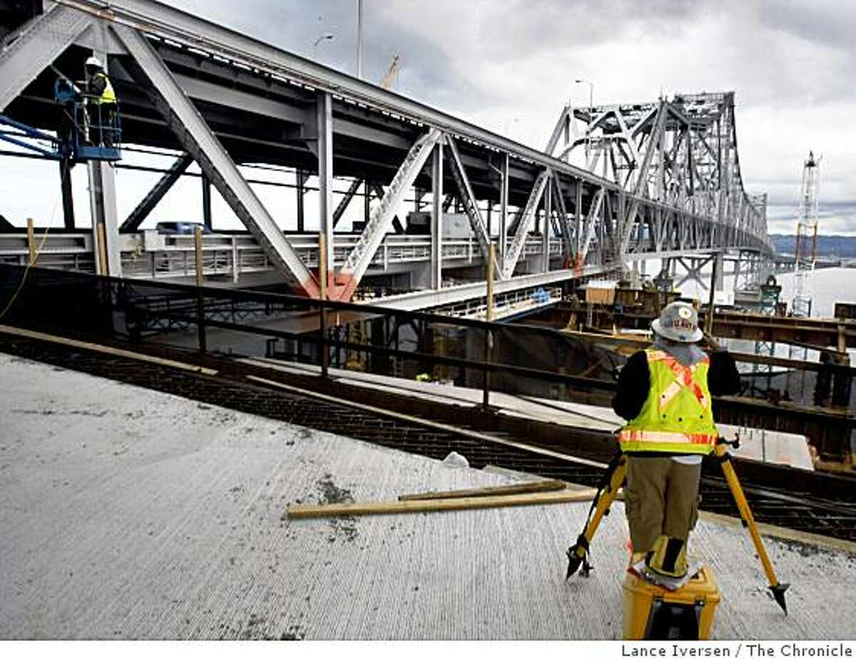 Surveyor Lori Delgado works at the end of the new temporary detour span of the San Francisco-Oakland Bay Bridge that will connect to the old gray steal portion of the bridge east of Yerba Buena Island.