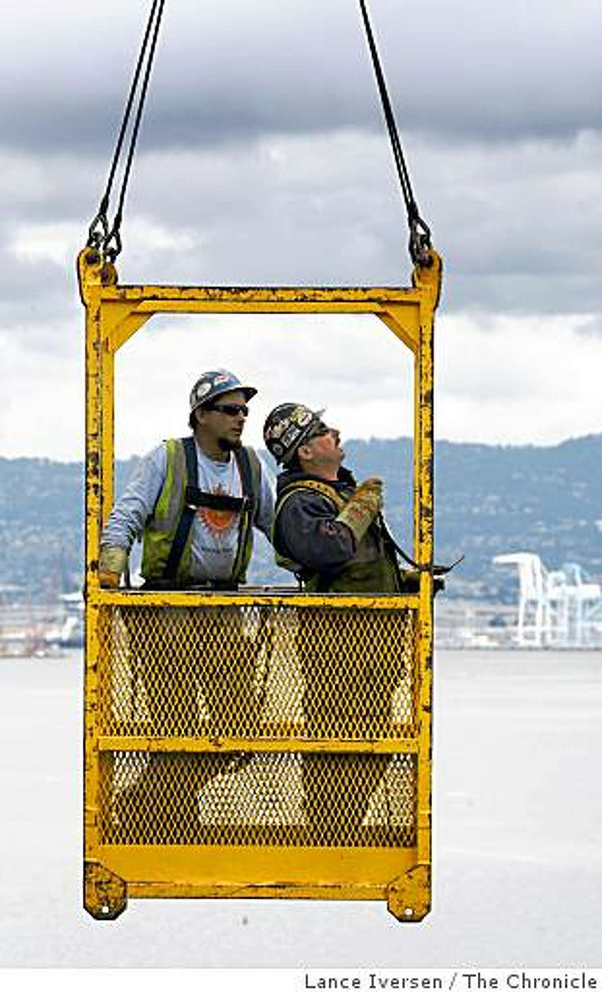 Iron workers are ferried with the use of a giant grane, between elevations as they work on the new temporary detour span of the San Francisco-Oakland Bay Bridge that will connect to the old gray steal portion of the bridge east of Yerba Buena Island Labor Day weekend. Wednesday, April 8, 2009