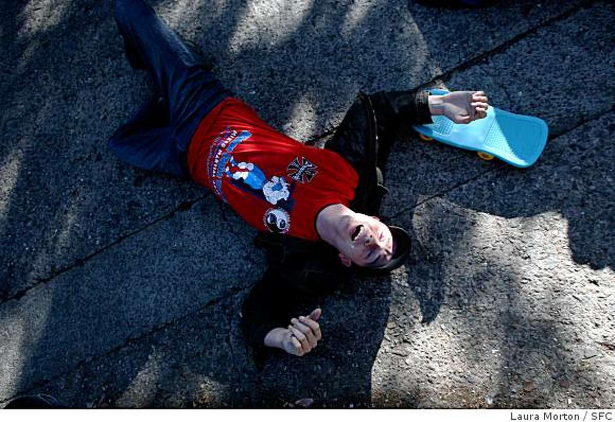 A participant in the 8th annual Bring Your Own Big Wheel Race lies on the ground after wiping out trying to make his way down Vermont Street in the Potrero Hill neighborhood of San Francsico on Sunday, March 23, 2008.