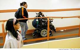 San Francisco's Mission High School senior Gaby Castro is able to glide her wheel chair throughout the campus including the hallways were as she meets with friends L to R Leslie Chang and Ana Quechol . The school has just completed a major facelift to accommodate disabled students. New elevators along with ramps provide access to 27 level changes found throughout the school Friday, April 3, 2009
