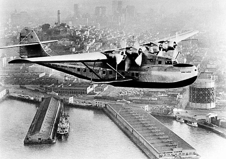 A Pan American Airways Martin M-130 flying boat, the China Clipper, leaves San Francisco Bay for Manila carrying the first United States trans-Pacific air mail on Nov. 22, 1935.  In the background is Coit Tower and the San Francisco skyline.  (AP Photo/PanAm) Photo: AP