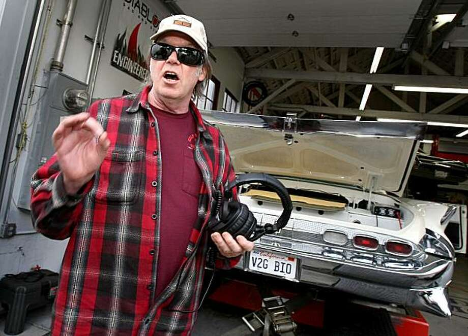 Neil Young explains how his Lincoln runs on CNG. Neil Young is teaming up with a company in Wichita, Kansas and Salesforce.com to promote the idea of converting existing gas-guzzling cars into vehicles that run on alternate energy. He stopped by a garage Sunday November 2, 2008 to test his 1959 Lincoln Continental. Photo: Brant Ward, The Chronicle