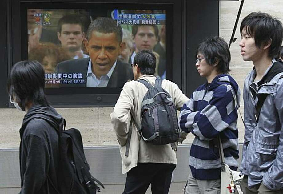 A man looks at a large TV screen showing U.S. President Barack Obama delivering a campaign speech, in central Tokyo Thursday, Nov 4,  2010. A chastened Obama signaled a willingness to compromise with Republicans on tax cuts and energy policy Wednesday, one day after his party lost control of the House and suffered deep Senate losses in midterm elections. Photo: Koji Sasahara, AP