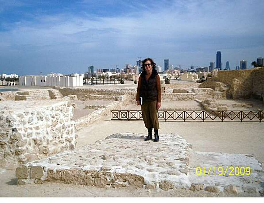 Details of attached photo (if sent): Diane Heinze at the Qala'At Al-Bahrain (Bahrain Fort).  5,000 layers of history juxtoposed with reconstruction and land reclamation in the backgroundDiane Heinze, OaklandEmail: dheinze@portoakland.comDaytime phone number: 510-627-1759Just back from: Manama, Kingdom of BahrainI went because: I went to Bahrain to visit good friends from Egypt who are teaching at Bahrain University and the New York Institute of TechnologyDon't miss: The Bahrain National Museum.  Experience the 7,000 year history of Bahrain (aka Dilmun and Tylos), and pearl hunting from springs under the sea.Don't bother: Bringing head coverings or trying to learn Arabic.  All styles of dress are accepted, and everyone speaks English.Coolest souvenir: T shirts for my son and husband bought at Bab (gate) al-Bahrain.  Bargaining is a sport in the Gulf for the buyer and the seller.Worth a splurge: Driving an hour south to the undeveloped portion of Bahrain to experience winter desert camping, dune buggy rides, and Arab hospitality (bbq) in tentsI wish I'd packed: Pictures of my family to show our guests and their friends.Other comments: Bahrain is a small island country influenced by Saudi Arabia (workers commute via a bridge), other Gulf countries, as well as Iraq and Iran