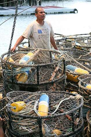 "First mate Cisco Gonzales and 3rd mate Daniel Kelly tie down 500 crab pots on the crab boat ""Madeline"" owned by captain Bob Burchell as they prepare to ship out for the opening of the Dungeness crab season in San Francisco, Calif, on Tuesday, November 16, 2010. Photo: Kat Wade, Special To The Chronicle"