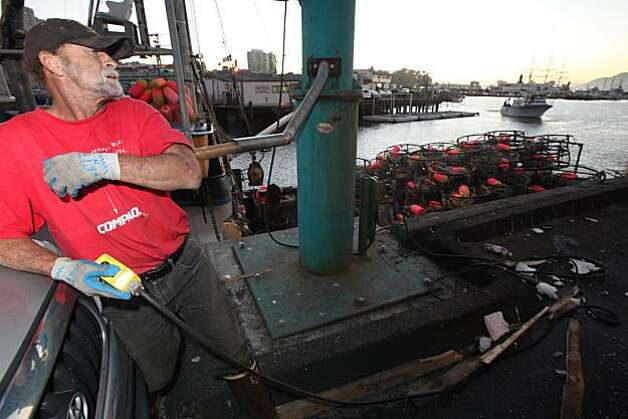 "Phillip Keeling loads crab pots aboard the ""Phantom"" as in the background Captain John Atkinson brings in the first 9,000 pounds of crab to Albers Seafood at pier 45 aboard his sports fishing boat ""New Rayann"" for the opening of the Dungeness crab season in San Francisco, Calif.., on Tuesday, November 16, 2010. Photo: Kat Wade, Special To The Chronicle"