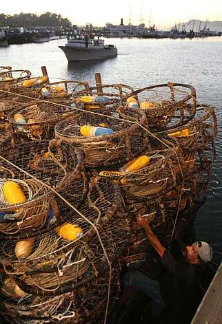 "Captain John Atkinson brings in the first 9,000 pounds of crab to Albers Seafood at pier 45 aboard his sports fishing boat ""New Rayann"" while deck hand Mitch Denny loads crab pots aboard the Madeline for the opening of the Dungeness crab season in San Francisco, Calif.., on Tuesday, November 16, 2010. Photo: Kat Wade, Special To The Chronicle"