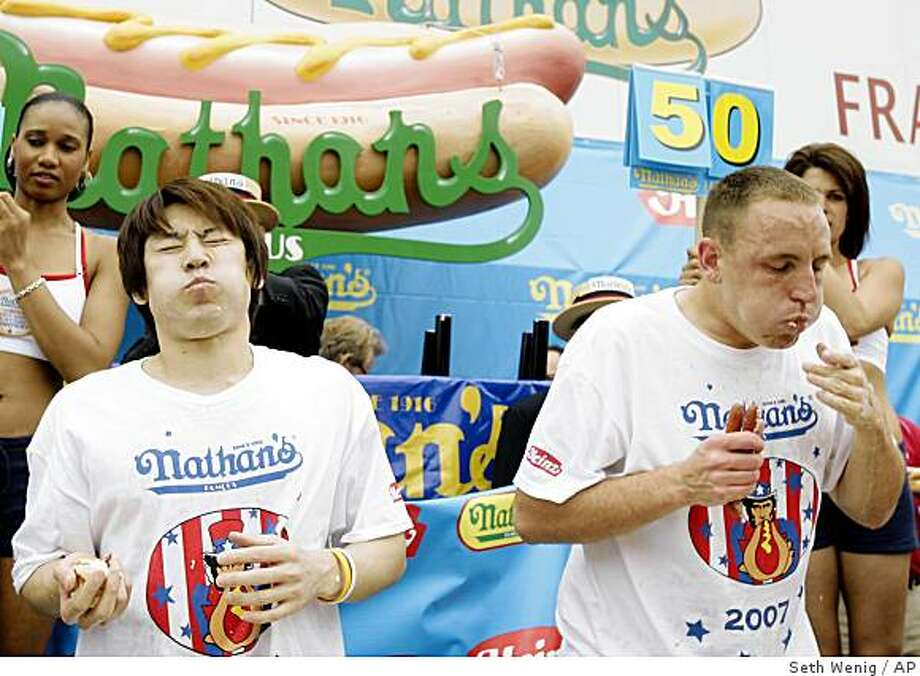 Takeru Kobayashi, left, and Joey Chestnut, right, eat hot dogs during Nathan's Famous Hot Dog Eating Competition in New York, Wednesday, July 4, 2007. In a gut-busting showdown that combined drama, daring and indigestion, Joey Chestnut emerged this afternoon as the world's hot dog eating champion by gobbling down a record 66 franks. The Californian knocked off six-time titlist Takeru Kobayashi in a rousing yet repulsive triumph in Coney Island. Photo: Seth Wenig, AP