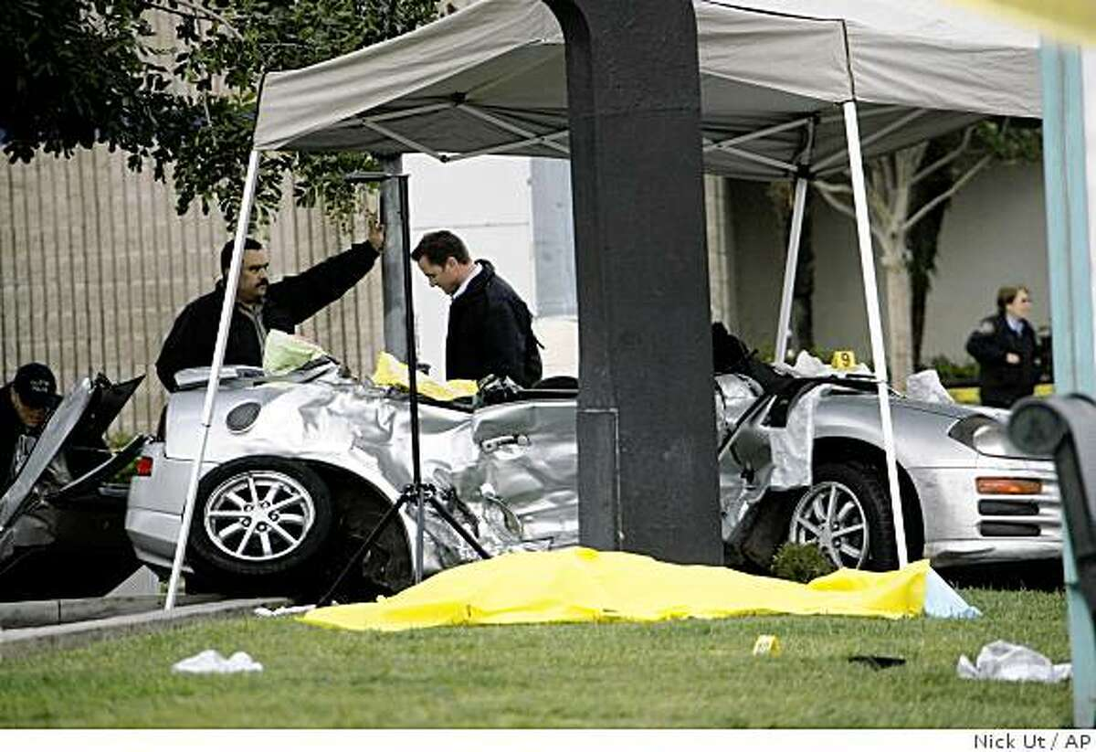 A body lays covered on the ground as investigators survey the scene of a hit-and-run car accident Thursday, April 9, 2009, in Fullerton, Calif, that claimed the life of Los Angeles Angels pitcher Nick Adenhart. Adenhart and two other people were killed early Thursday hours after his season debut when a minivan ran a red light and struck their sports car, authorities said. (AP Photo/Nick Ut)