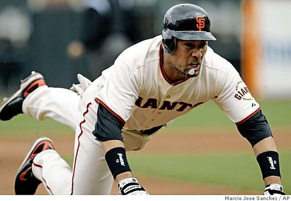 San Francisco Giants' Travis Ishikawa dives into third base on his three-run triple against the Milwaukee Brewers in the first inning of opening day in San Francisco, Tuesday, April 7, 2009.