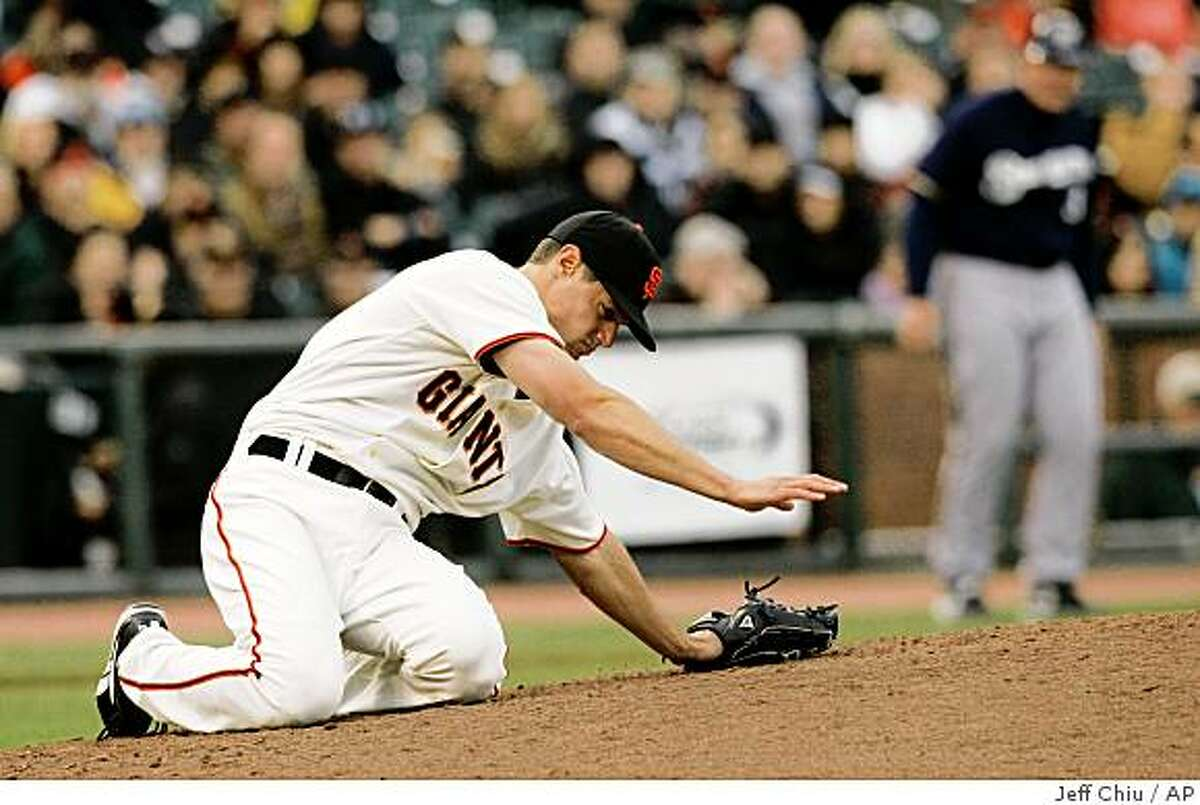 San Francisco Giants' Joe Martinez reacts after being hit in the head by Milwaukee Brewers' Mike Cameron's double in the ninth inning in San Francisco on Thursday. The Giants won, 7-1. Martinez left the game.
