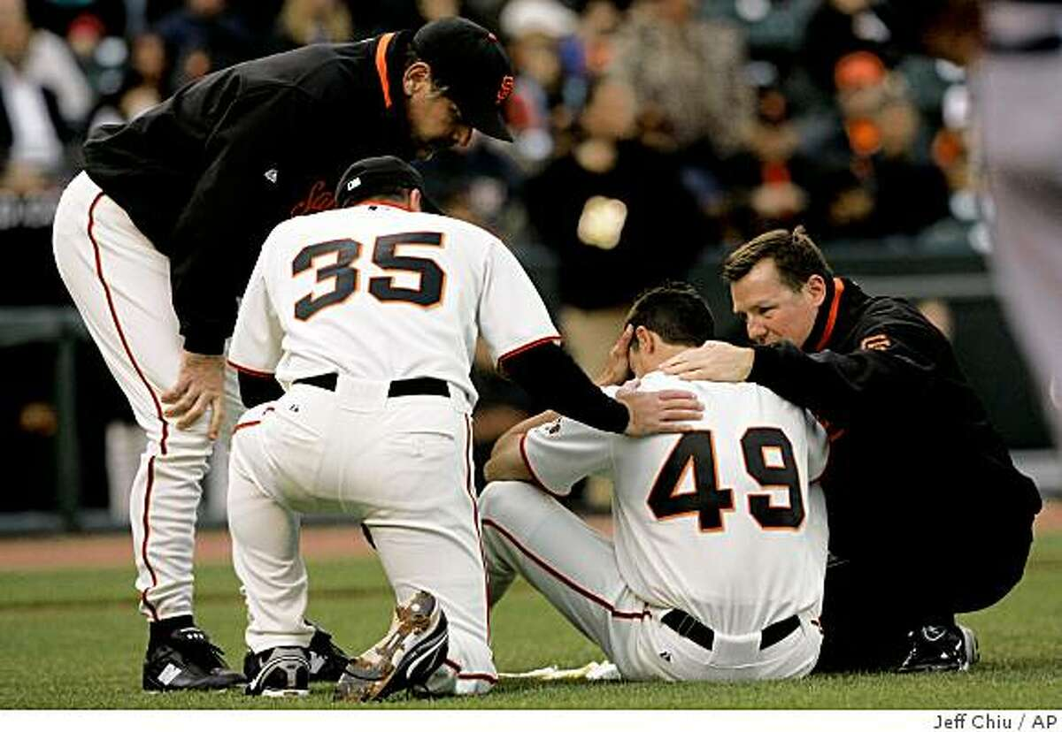 San Francisco Giants' Joe Martinez, second from right, is tended to by head trainer Dave Groeschner, right, manager Bruch Bochy, top left, and Rich Aurilia after being hit in the head by Milwaukee Brewers' Mike Cameron's double in the ninth inning of a baseball game in San Francisco, Thursday, April 9, 2009. The Giants won 7-1. Martinez left the game. (AP Photo/Jeff Chiu)