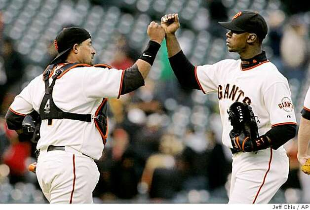 San Francisco Giants' Bengie Molina, left, celebrates with Fred Lewis after the final out of the ninth inning of a baseball game against the Milwaukee Brewers in San Francisco on Thursday. The Giants won 7-1. Photo: Jeff Chiu, AP