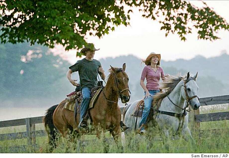 """In this image released by Disney Enterprises, Miley Cyrus, right, and Lucas Till are shown in a scene from """"Hannah Montana: The Movie."""" (AP Photo/Disney Enterprises, Sam Emerson) ** NO SALES ** Photo: Sam Emerson, AP"""