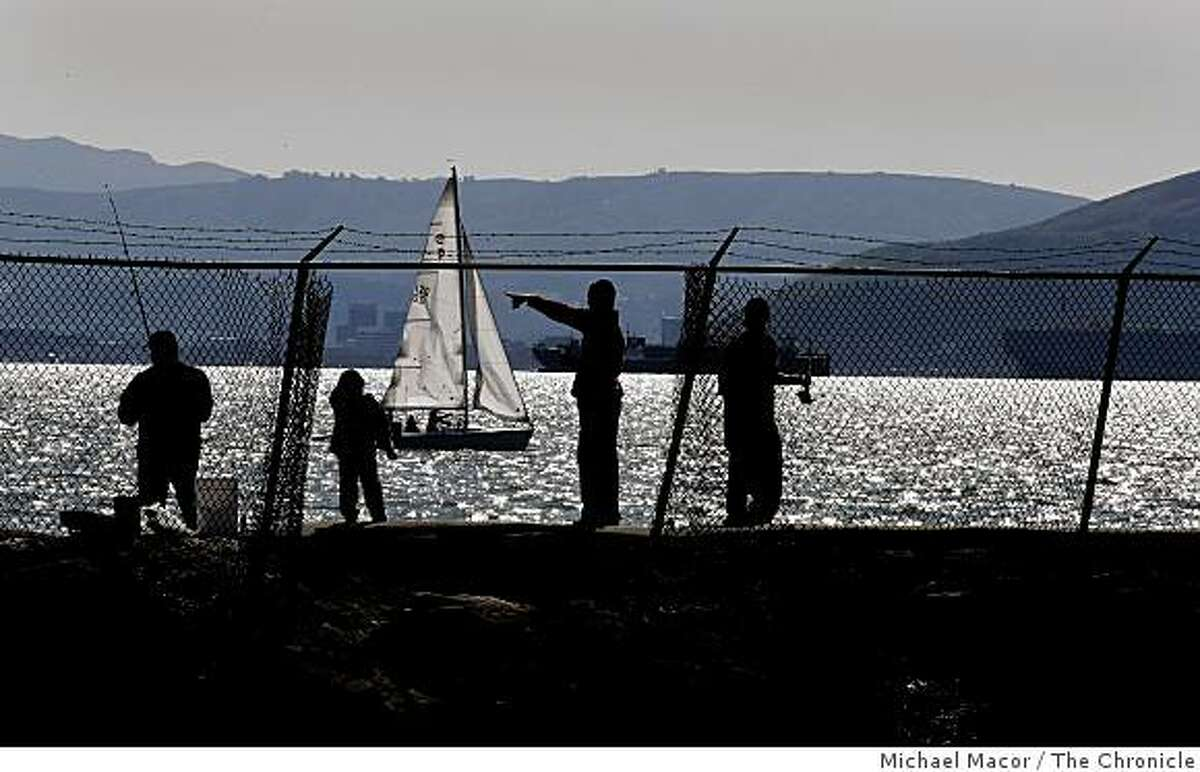 Rafael Recarte, (left) with his three sons, (left to right) Jossue, Olberth and Dennis enjoying the sunny day fishing off the breakwater at Alameda Point in Alameda on Tuesday Mar. 10, 2009.