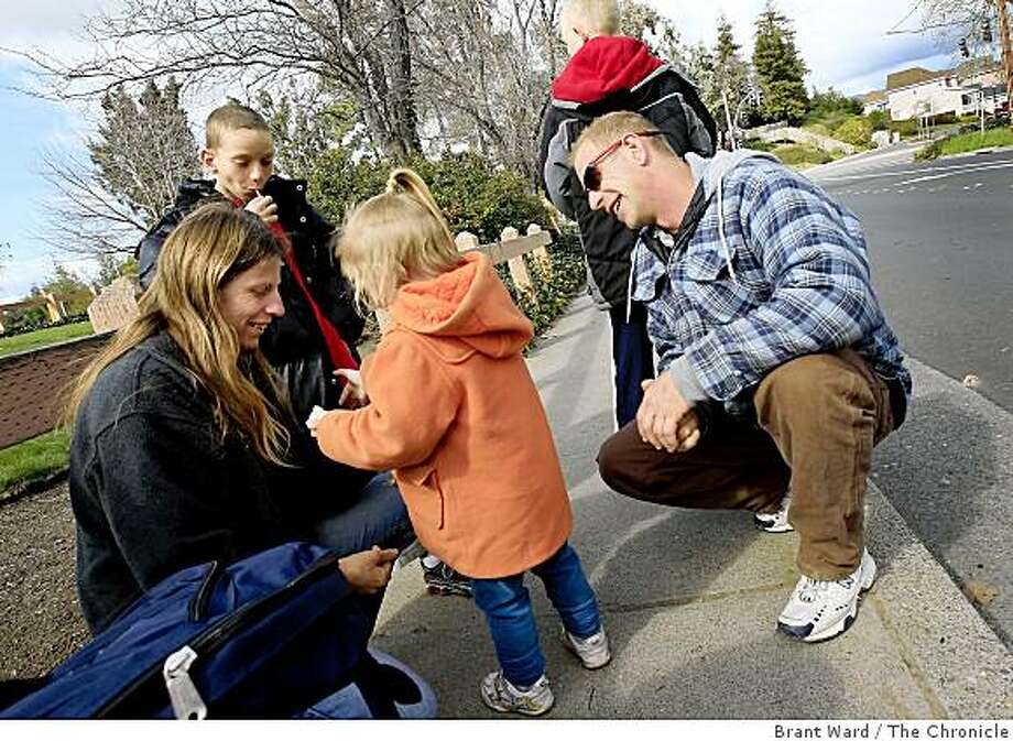 Sharina Grimes (left) and Phillip Scardino (right) greet their children: Kole, Trashelle and Travis, after school in Petaluma. Phillip Scardino and Sharina Grimes and their three children came to California for a job that didn't work out in this difficult economy. After staying in Marin County for a time, they found themselves in Petaluma staying at a family shelter. Photo: Brant Ward, The Chronicle