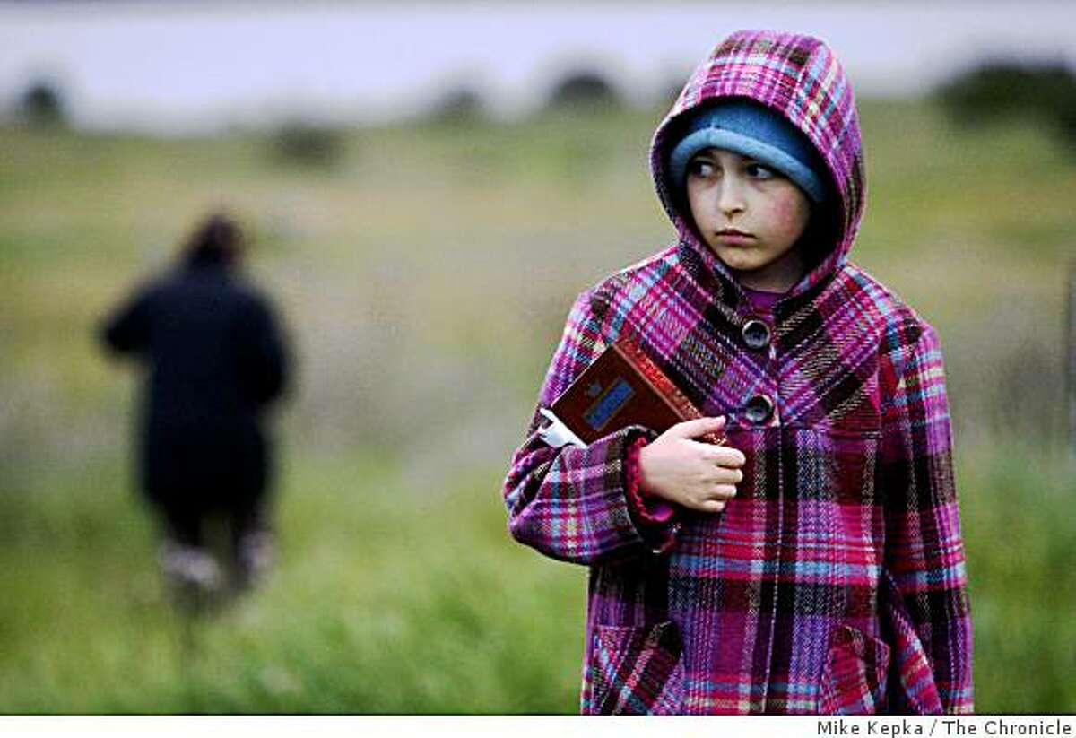 Adira Tharan, 9, of El Cerrito clutches her siddur as she joins others Jews from around the Bay Area gathering to observe a once-in-a-generation ritual of blessing the sun at the Cesar Chavez Solar Calendar in Cesar Chavez Park on Wednesday April 8, 2009 in Berkeley, Calif.