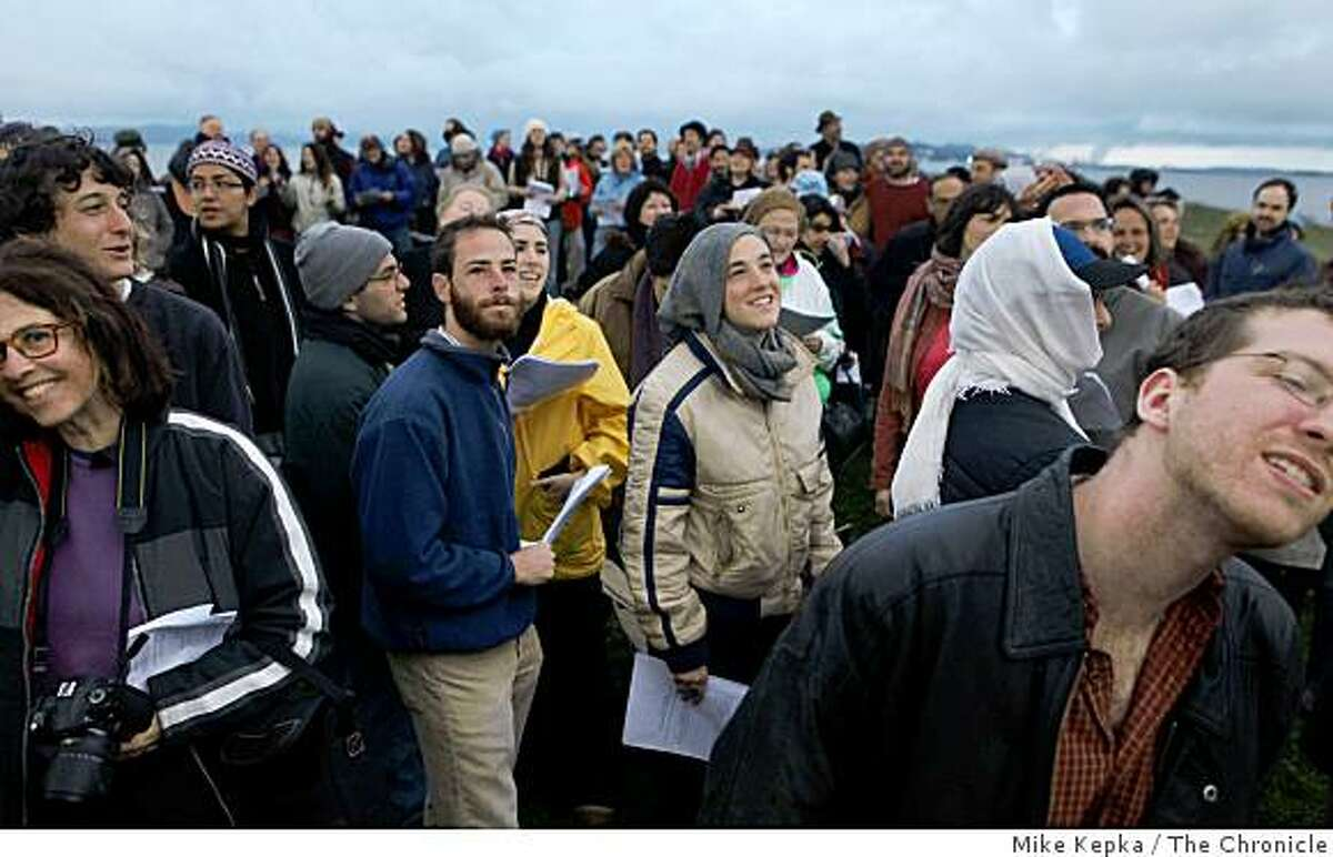 As the sun starts to rise, Adam Edell (center left) and Vanessa Greenfield (center right) join of a group of other Jews from around the Bay Area who gather to observed a once-in-a-generation ritual of blessing the sun at the Cesar Chavez Solar Calendar in Cesar Chavez Park on Wednesday April 8, 2009 in Berkeley, Calif.