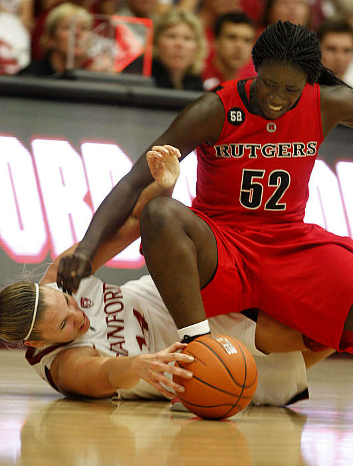 Stanford's Kayla Pedersen (14) and Rutgers' Chelsey Lee battle for a loose ball in the second period at Maples Pavilion on Sunday.