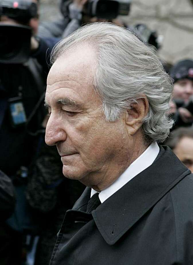 FILE - In this March 10, 2009 file photo, Bernard Madoff exits Manhattan federal court in New York. Two former computer programmers for Bernard Madoff's investment firm were arrested Friday, Nov. 13, 2009, on charges they helped cover up the disgraced money manager's massive fraud for more than 15 years. (AP Photo/David Karp, file) Photo: David Karp, File, AP