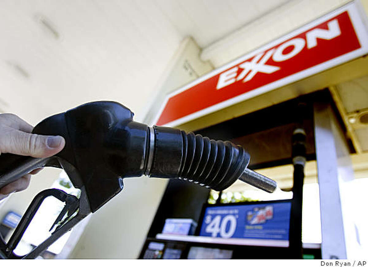 ** FILE ** In this July 31, 2008 file photo, a customer holds a gas pump handle at an Exxon station in Vancouver, Wash. Exxon Mobil Corp. sets quarterly profit record for U.S corporations at $14.83 billion, Thursday, Oct. 30, 2008.(AP Photo/Don Ryan, file)