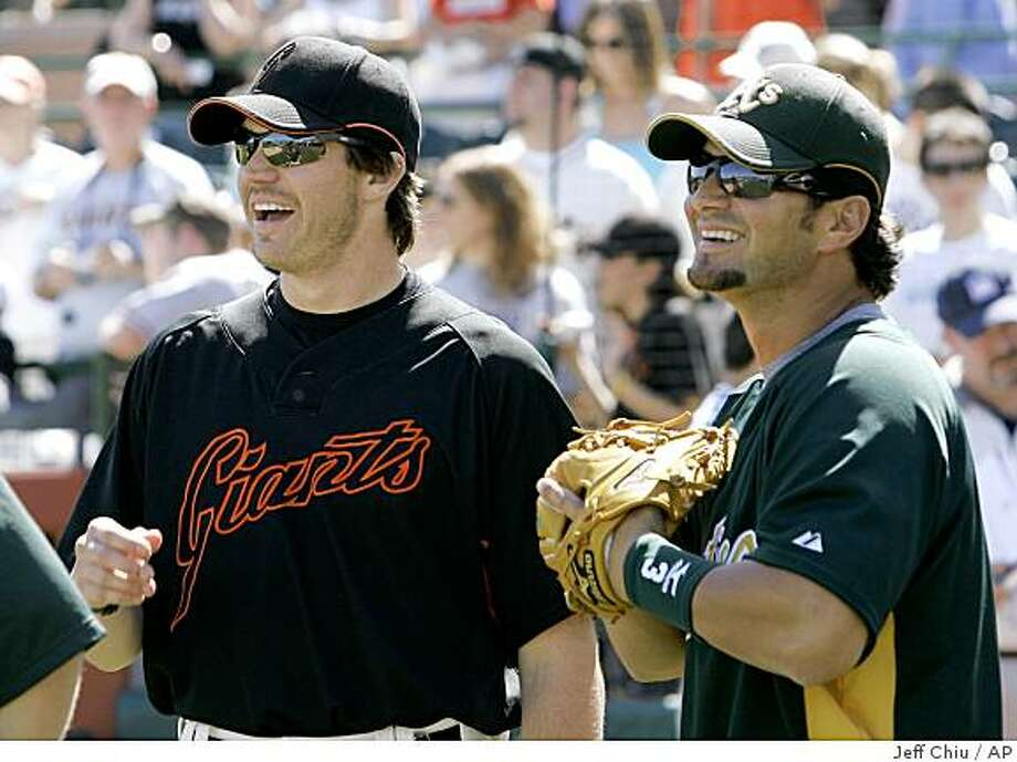 San Francisco Giants pitcher Barry Zito, left, talks with Oakland Athletics' Eric Chavez before the two teams played in a spring training baseball game in Scottsdale, Ariz., Friday, March 9, 2007. (AP Photo/Jeff Chiu) Photo: Jeff Chiu, AP