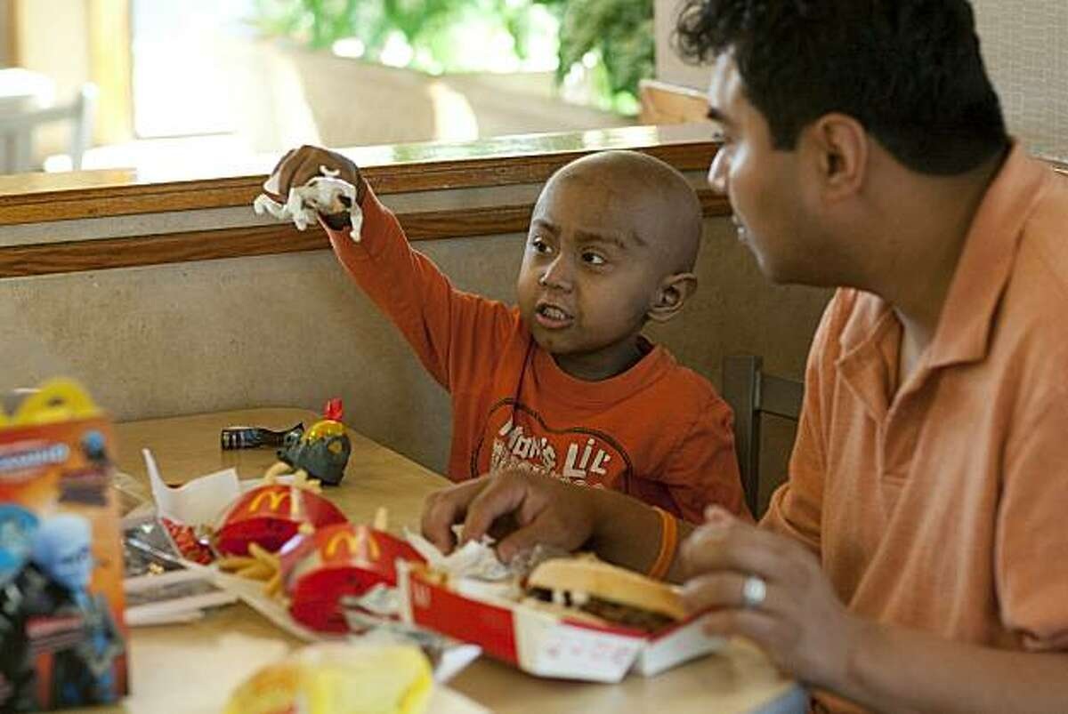 SAN FRANCISCO, CA - NOVEMBER 03: Five-year-old Andy Villatoro plays with a toy he received after ordering a Happy Meal at McDonald's as his father Carlos Villatoro (R) watches on November 3, 2010 in San Francisco, California. San Francisco became the first city in the nation to pass a law to control giving away free toys with unhealthy meals for children. The law requires that any restaurant kid's meals meet nutritional standards before they can be sold with toys.