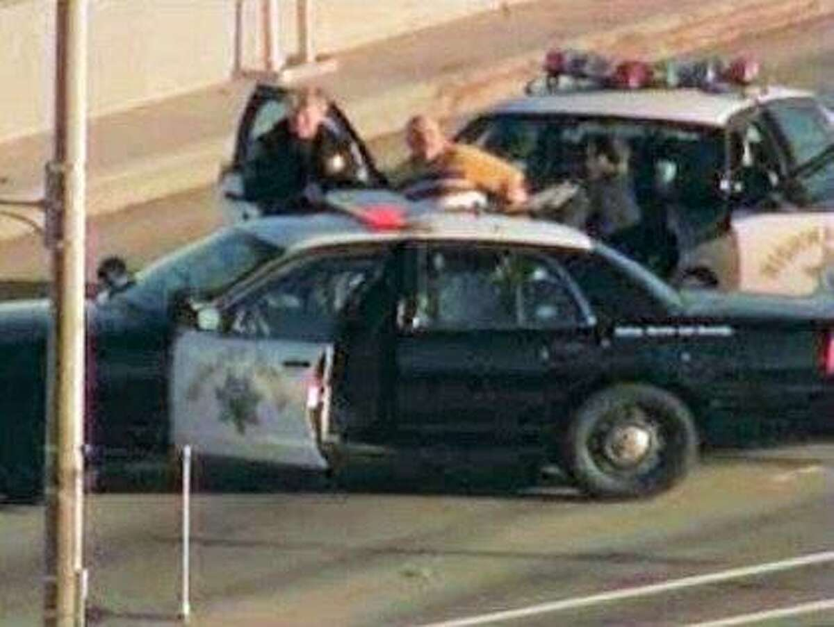 A man is taken into custody by CHP officers following an hour-long standoff on the upper deck of the Bay Bridge Thursday morning.