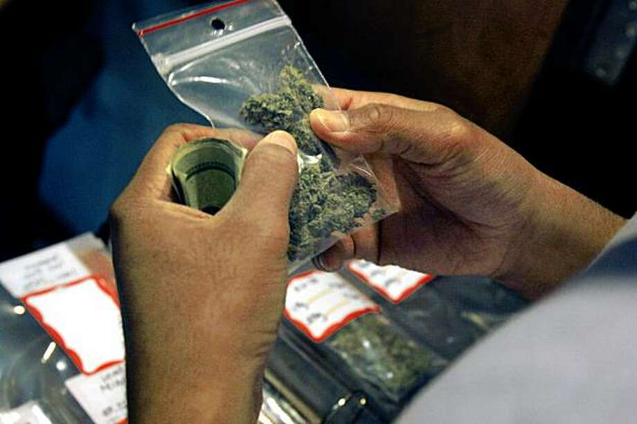 A patrons inspects a bag of marijuana while filling their medical marijuana prescription at the Coffeeshop Blue Sky in Oakland, Calif. on Monday October 19, 2009. Photo: Lea Suzuki, The Chronicle
