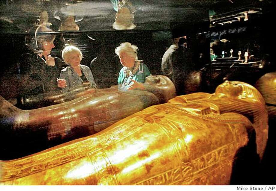 "This photo released by the Dallas Museum of Art shows, from left, Phyllis Hammond of the Dallas Convention and Visitors Bureau, Judy Pollock of the City of Dallas and Dallas Museum of Art Curator Anne Bromberg as they view the Gilded Coffin of Tjuya artifact at a media event Wednesday, Oct. 1, 2008, at the Dallas Museum of Art as it prepares for the public opening Friday of ""Tutankhamun and the Golden Age of the Pharaohs"", in Dallas. (AP Photo/Mike Stone) Photo: Mike Stone, AP"