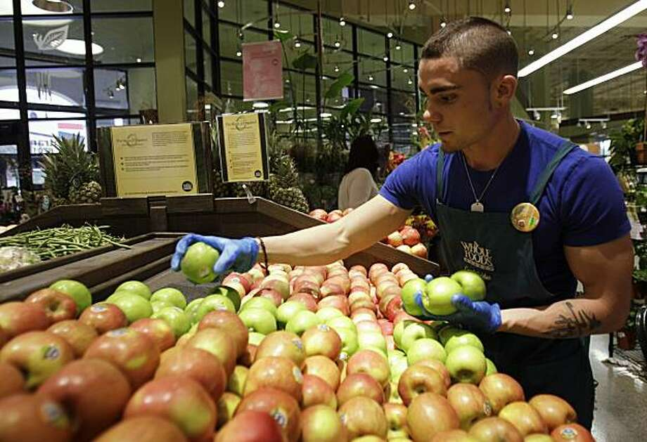 Victor Hernandez stocks apples in the produce section at Whole Foods, Wednesday, Nov. 3, 2010, in Coral Gables, Fla. Whole Foods Market Inc. more than doubled its fourth-quarter net income as sales rose, prompting the grocer to raise its full-year outlookon Wednesday. Photo: Lynne Sladky, AP