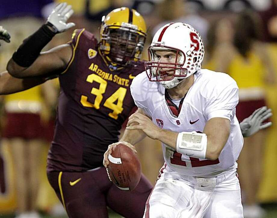 Stanford quarterback Andrew Luck, front, escapes the grasp of Arizona State defensive end James Brooks during the second half of an NCAA football game Saturday, Nov. 13, 2010, in Tempe, Ariz. Stanford won 17-14. Photo: Matt York, AP