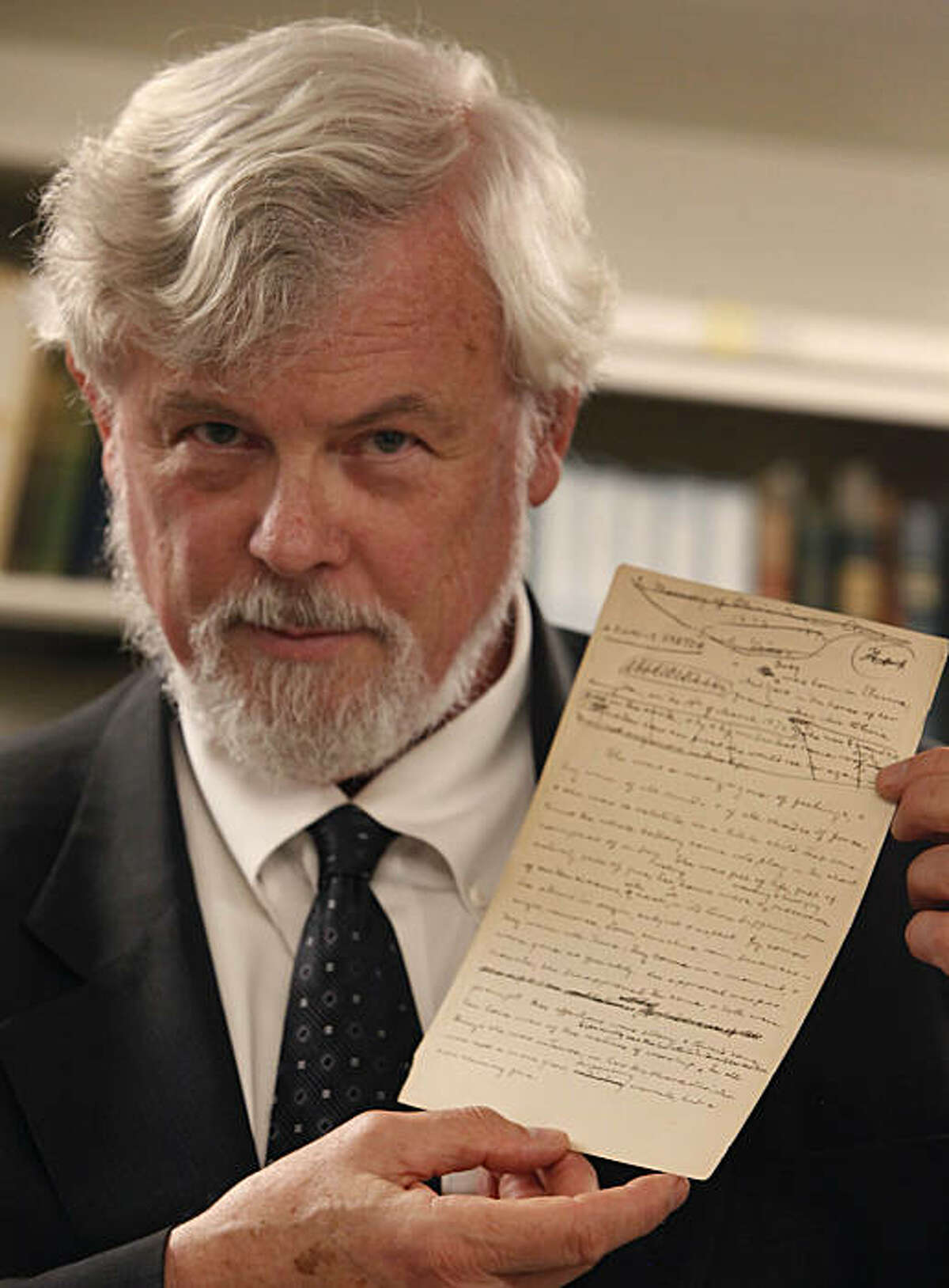 """Robert Hirst, general editor Mark Twain Project, holds the first page of """"A Family Sketch"""", a recent acquisition for UC Berkeley, in the Mark Twain Papers vault at the Bancroft Library at UC Berkeley on Friday, November 5, 2010 in Berkeley, Calif."""