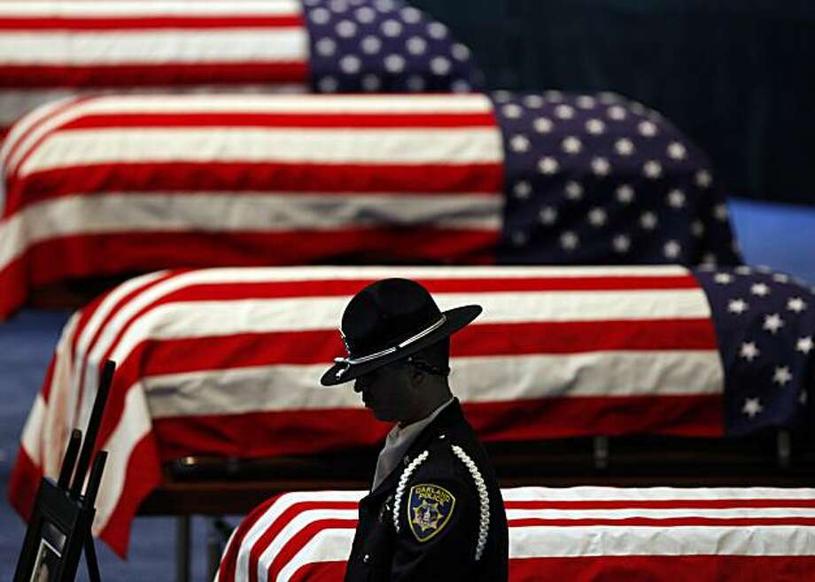 An Oakland Police honor guard stands his post next to the flag-draped caskets of Oakland Police Officers Sgt. Mark Dunakin, 40; John Hege, 41; Sgt. Ervin Romans, 43; and Sgt. Daniel Sakai, 35, are carried by law enforcement officers into Oracle Arena on Friday, Mar. 27, 2009, in Oakland, Calif. Thousands of officers and firefighters from around the nation and overseas along with mourners turned out for Friday's funeral for the four veterans. The four officers were shot in the line of duty Saturday, March 21. (Michael Macor/ San Francisco Chronicle, Pool) Photo: Michael Macor, The Chronicle