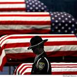An Oakland Police honor guard stands his post next to the flag-draped caskets of Oakland Police Officers Sgt. Mark Dunakin, 40; John Hege, 41; Sgt. Ervin Romans, 43; and Sgt. Daniel Sakai, 35, are carried by law enforcement officers into Oracle Arena on Friday, Mar. 27, 2009, in Oakland, Calif. Thousands of officers and firefighters from around the nation and overseas along with mourners turned out for Friday's funeral for the four veterans. The four officers were shot in the line of duty Saturday, March 21. (Michael Macor/ San Francisco Chronicle, Pool)