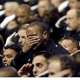 An Oakland police officer reacts on Friday, March 27, 2009 at the Oracle Arena in Oakland, Calif., where a funeral was held for Oakland Police Officers Sgt. Mark Dunakin, 40, John Hege, 41, Sgt. Ervin Romans, 43, and Sgt. Daniel Sakai, 35, in Oracle Arena on Friday, Mar. 27, 2009, in Oakland, Calif. Thousands of mourners have gathered with the families of four slain Oakland police officers for a joint funeral that drew law enforcement from around the world.(AP Photo/Jane Tyska, Pool)