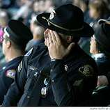 OAKLAND, CA - MARCH 27:  Sgt. Joe Flannagan of the Alhambra police department wipes his eyes he watches funeral services for four Oakland police officers March 27, 2009 in Oakland, California. Thousands of police officers from across the country along with members of the public came out to pay their respects to four Oakland police officers that were killed in the line of duty last Saturday following a traffic stop of a fugitive parolee. Over 15,000 people attended the memorial service.  (Photo by Justin Sullivan/Getty Images)