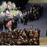 OAKLAND, CA - MARCH 27:  The first of the four flag draped caskets of Oakland Police Officers Sgt. Mark Dunakin, 40, John Hege, 41, Sgt. Ervin Romans, 43, and Sgt. Daniel Sakai, 35, is carried in by law enforcement officers into the arena for funeral services for four Oakland police officers on Oracle Arena on March 27, 2009 in Oakland, California. Thousands of police officers from across the country along with members of the public came out to pay their respects to four Oakland police officers the were killed in the line of duty last Saturday following a traffic stop of a fugitive parolee. (Photo by Michael Macor-Pool/Getty Images)