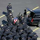 The flag draped casket of one of the slain Oakland Police Officers is taken into the arena during funeral services for four Oakland police officers at Oracle Arena on March 27, 2009 in Oakland, California. Thousands of police officers from across the country along with members of the public came out to pay their respects to four Oakland police officers the were killed in the line of duty last Saturday following a traffic stop of a fugitive parolee.