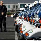 OAKLAND, CA - MARCH 27:  A San Francisco police officer stands near a row of police motorcycles during funeral services for four killed Oakland police officers March 27, 2009 in Oakland, California. Thousands of police officers from across the country along with members of the public came out to pay their respects to four Oakland police officers the were killed in the line of duty last Saturday following a traffic stop of a fugitive parolee.  (Photo by Justin Sullivan/Getty Images)