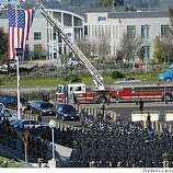 Police officers from across the country and Bay Area residents stood at attention outside the Oracle Arena on Friday March 27, 2009 in Oakland, Calif., for the arrival the the four slained Oakland police officers shot and killed in the line of duty.